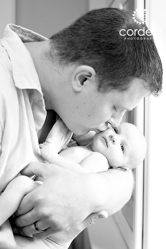 black and white photo of dad kissing baby