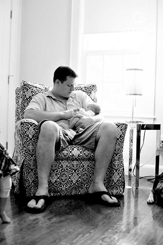 dad and baby sit in rocking chair.
