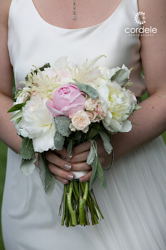A bride holds a white boutque with pink flowers