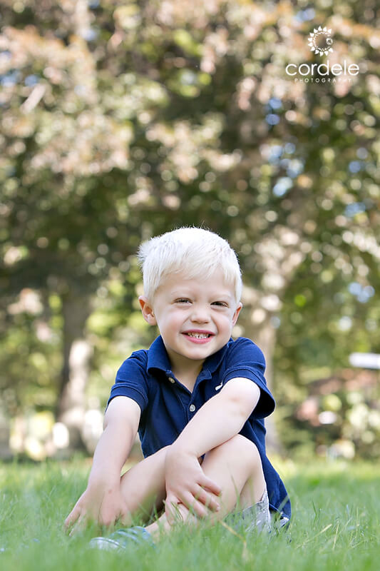 Little boy sitting on grass together