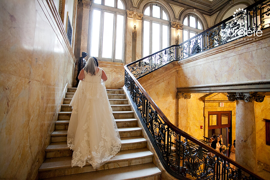 Bride walking upstairs of providence public library