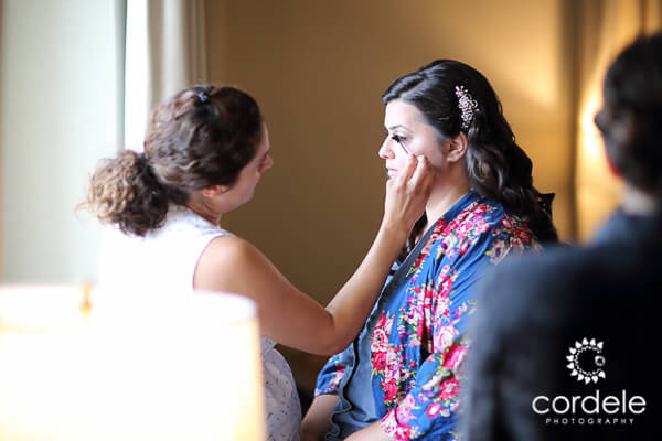 A bride sits in front of a window at the Biltmore Hotel getting her makeup done by Fab Browz make up artist