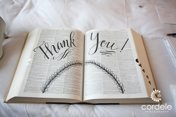 A dictionary sits on a bed with it opened to the middle and the words THANK YOU stencilled on it.