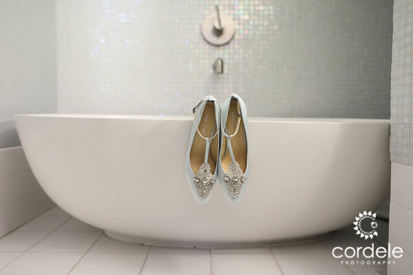 Light blue shoes hang over the bathtub ledge at the Providence Biltmore Hotel