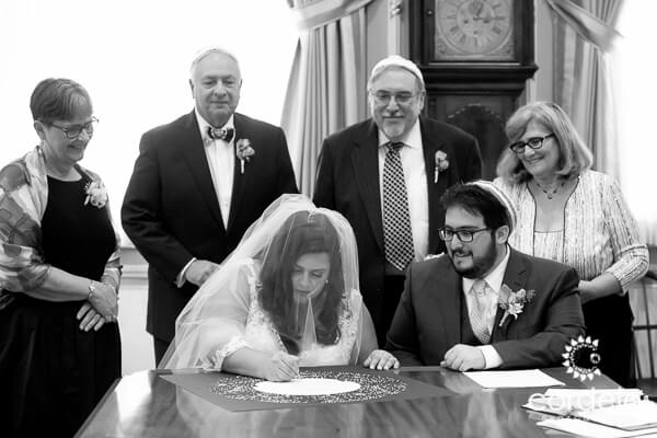 Black and White photo of bride and groom signing Ketubah