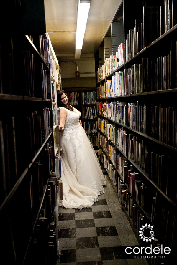 a bride leans against a stack of books.  She is under a florescent light and the books are 5 shelves high