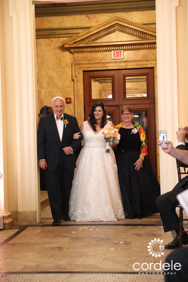 A brides parents walk her down an aisle at the Providence Public Library
