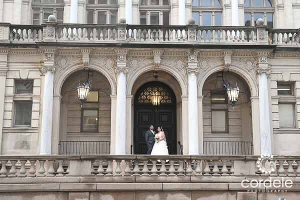 A bride and groom stand in front of the Providence Public Library